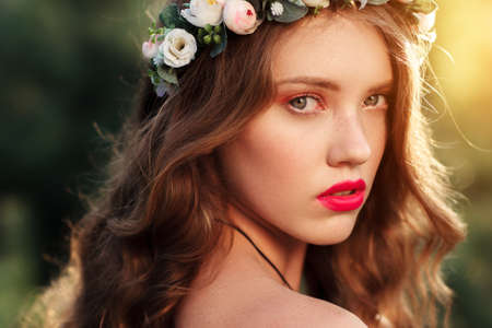 Portrait of attractive girl in wreath at sunset. Half-turned young beautiful woman with red lips and fashion look close-up. Stock Photo