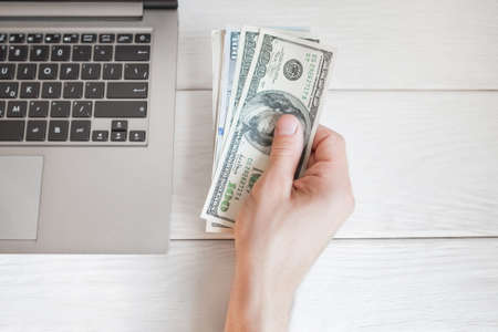 hand lay: Man holding dollars near laptop, free space, flat lay. Top view on male hand with batch of american bucks near notebook, whote wooden background. Finance and earning concept Stock Photo