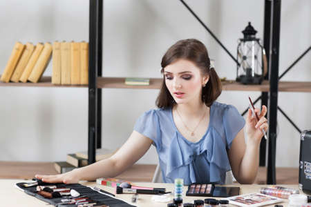 importance: Professional visagiste choosing brush for makeup. Artist tells about importance of each tool for visage making. Beauty, fashion, cosmetics concept