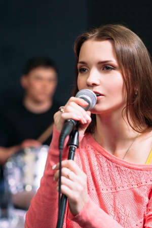 Young attractive woman singing karaoke in bar. Beautiful girl enjoying her evening pastime with microphone, close-up portrait Stock Photo