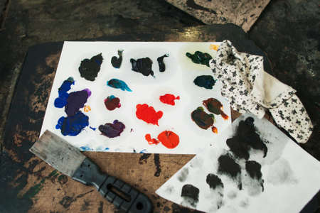 Colorful mixed oil paint smears with palette-knife. Samples of different colors on paper palette. Close-up of artist workplace with swatches