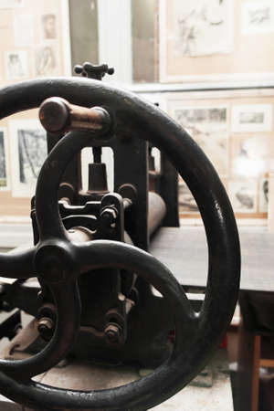 Grip of ancient handle printing press, close-up. Old iron printery equipment, spindle with rusty gears. Ancient publishing house instrument Stock Photo