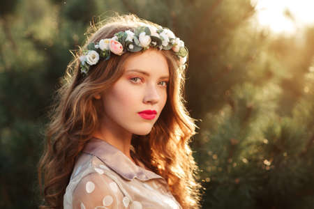 pinetree: Semi profile portrait of beautiful girl in wreath, free space. Attractive young smiling woman in forest, blurred pine-tree background, sunset light.
