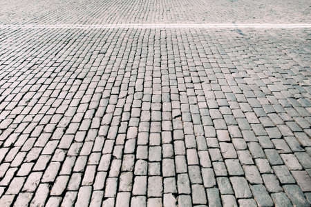 cobblestone road: Paving stone square texture. Closeup view on cobblestone road with white lines. Outdoor street background, free space