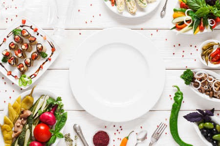 White ceramic plate surrounded by snacks, void. Variety of vegetarian meals make frame for empty dish. Cuisine, menu, food concept