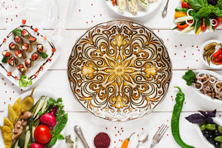 free dish: Beautiful ethnic plate in center of food, void, flat lay. Dish with golden mandala ornament surrounded of vegetarian snacks, free space Stock Photo
