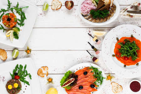 text space: Delicious mediterranean snacks on white table, free space, flat lay. Tasty plates with various salads, smoked fish and meat on white wooden background, copy space for text
