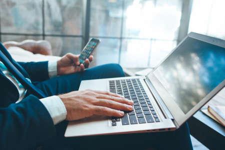 Hombre sentado con el ordenador portátil y el teléfono inteligente. Medios de comunicación. Los dispositivos modernos que utilizan.