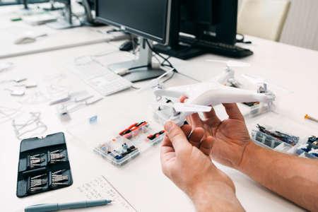 Close-up van drone in reparateurhanden, elektronische stuk speelgoed reparatiewerkplaats. Werkplek voor elektricien met vast onbemand luchtvaartuig. Business, elektronische constructie, moderne technologie concept