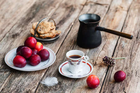lonelyness: Fresh tasty autumn breakfast. Cup of coffee with cookies, fresh plums and coffee pot on old rustic wooden table