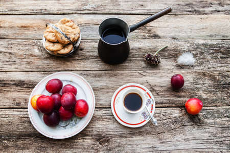 lonelyness: Inspirational early morning breakfast in country, flat lay. Top view on old rustic wooden table with fresh coffee in cup and pot, tasty plums and cookies.