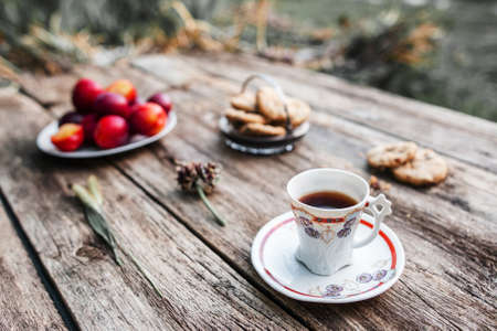 lonelyness: Cup of coffee on wooden table outdoor, Focus on cup, blurred background of fresh plums, cookies and green nature environment