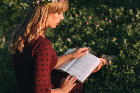 free space: Beautiful blonde with book profile, copy space. Young woman in red dress and wreath relaxing in blooming meadow, free space on green grass with flowers background.
