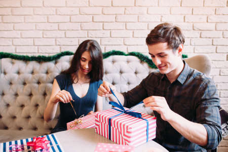 Happy couple unpacking xmas presents. Young happy man and woman giving gifts to each other. Christmas Eve, joy, winter holiday concept Stock Photo