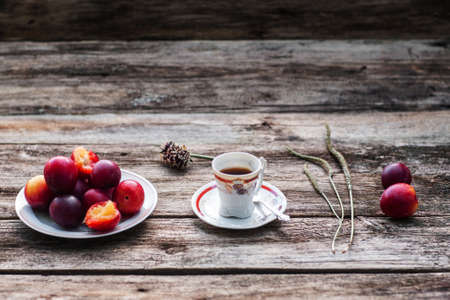 lonelyness: Cup of coffee and fresh plums on wood, free space. Warming drink with tasty fruit on old rustic wooden background, copy space for text