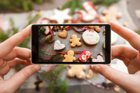 Hands taking picture of gingerbread cookies. Close-up photo of smartphone photographing traditional Christmas treat assortment. Food photography concept