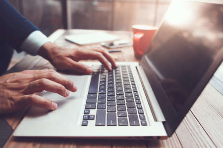 passions: Male hands typing on laptop on desk. Creative writing activity. Blogging. Stock Photo