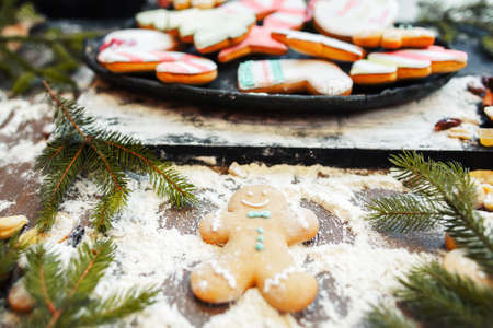 home decorating: Snow angel by gingerbread man on kitchen table. Christmas traditional treat preparing, home decorating. Fun at kitchen, cooking art, New Year pastry composition Stock Photo