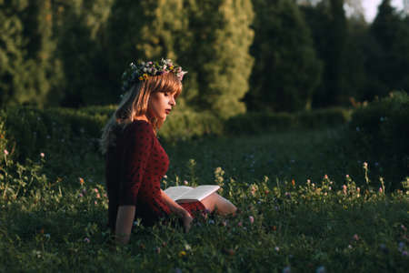 Attractive woman in wreath reading in nature, copy space. Young blonde sitting with book in blooming meadow. Summer, relax, freshness, loneliness concept Imagens