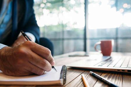 Mannelijke hand die nota's over de blocnote neemt. Handschrift. Creatief schrijven. Inscriptie of opname van tekens en symbolen.