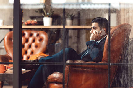 importer: Successful businessman sitting in firm. Side view on man talking on phone. Professional activity. Advising. Counseling. Trading. Stock Photo