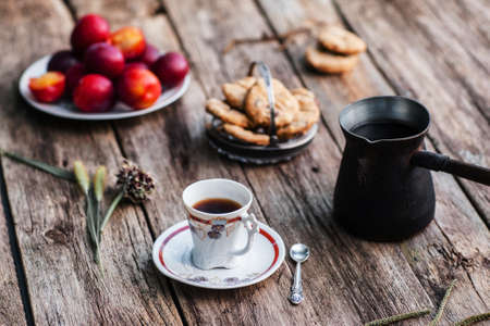 lonelyness: Cup of coffee and pot with different tasty snacks on wood. Ol rustic table served for traditional turkish coffee break with sweet cookies and fresh plums