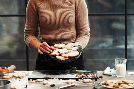 생강 빵 쿠키, 여유 공간이있는 빵을 들고 베이커. 준비 된 전통적인 크리스마스와 새 해 여성의 손의 근접 치료.