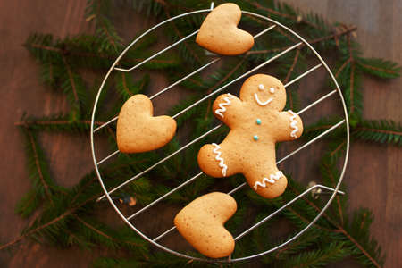 Gingerbread man and heart on grille. Christmas traditional cookies with pine-tree branches. Winter composition, xmas spirit, cooking concept