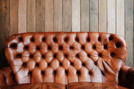 old furniture: Old leather sofa on wooden background, void. Shabby used luxury furniture, free space on plank wall