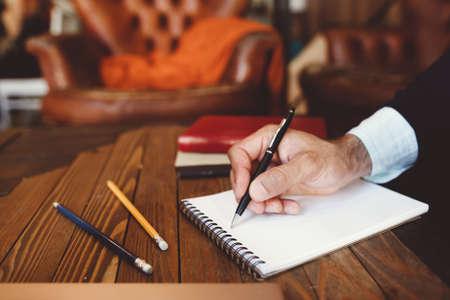ノートに書くペンを持つ手のアップ。通信の概念、情報交換、手紙を書いて、個人とビジネスの対応