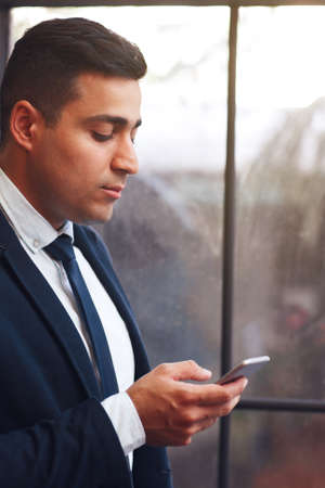 businesslike: Businesslike man looking into smartphone. Arabian man chatting with business partners.Telephone, modern technology, virtual communication concept.
