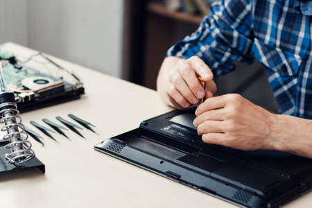 unscrewing: Laptop disassembling in repair shop, close-up. Engineer hands unscrewing computer part in repair shop