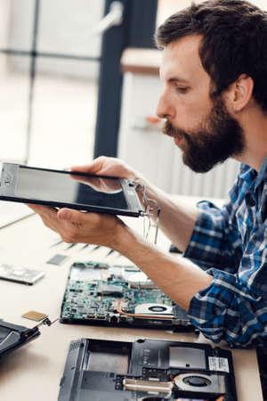 L'ingénieur souffle l'écran numérique hors poussière. Démontage d'ordinateur portable dans un atelier de réparation électronique. Renouvellement de la technologie, profession, concept d'entreprise Banque d'images - 65140926