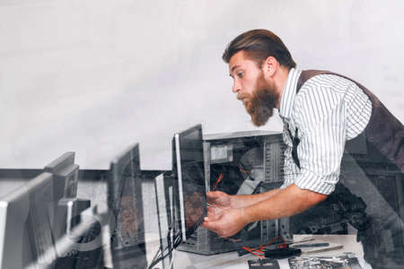 computer equipment: Computer monitor tuning in office, double exposure. Bearded system administrator fixing broken screen in open space. Repair, work, electronic concept