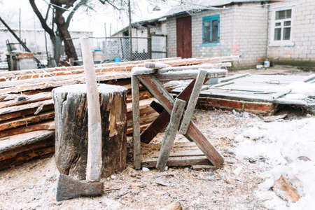 sawhorse: Sawhorse in winter yard. Russian winter. Place for firewood chopping, house on background. Cold, early frosts, hoar concept Stock Photo