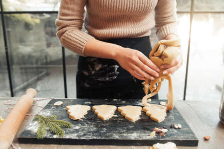Confectioner forming Christmas tree cookies on tray. Woman cook preparing dough for gingerbread treat bakery. Culinary classes, pastry cooking, homemade cuisine concept 스톡 콘텐츠