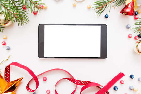 Smartphone with blank screen in Christmas frame, mockup. New year trumpery and empty smartphone on white background, copy space for text or advertisement, void