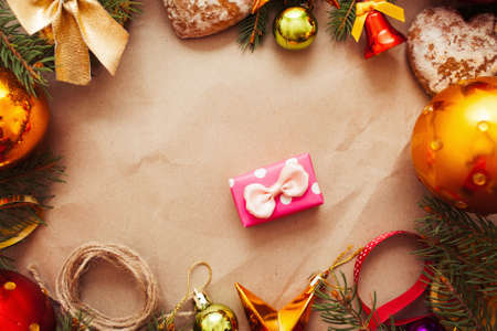Tiny pink gift in Christmas decorations frame. Festive composition on brown paper with New year trumpery and present box, free space