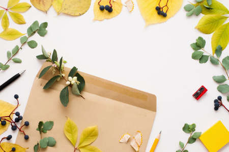 Brown envelope in autumn leaves frame, copy space. Vintage paper cover with green and yellow leaves on white background. Fall inspiration, creativity concept