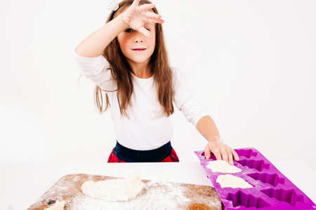 christmas baker's: Tired girl with floured hands on kitchen. Little confectioner forming cakes, free space on white background. Homemade bakery, children culinary, pastry making concept Stock Photo