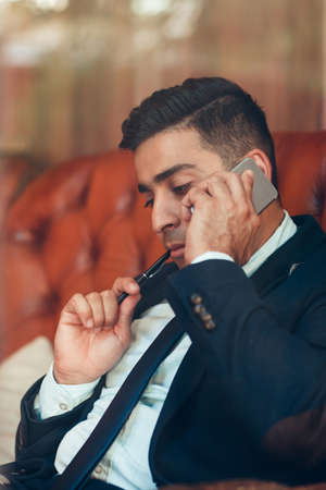 negotiating: Thoughtful man negotiating on the phone. Businessman solving complex business problems. Brainstorm. Teamwork.