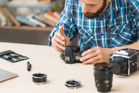 Disassembling of photo camera, close-up. Photographing equipment maintenance and repair. Hobby, occupation, business Stock Photo - 65150690