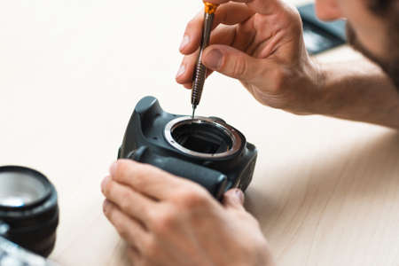 Disassembling of photo camera, close-up. Photographing equipment maintenance and repair. Hobby, occupation, business Stock Photo