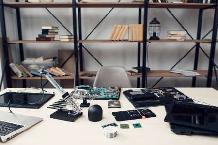 Electronic repair shop, workplace of engineer repairing technology. Table with necessary tools and equipment for electronics renovation. Work, occupation, business concept