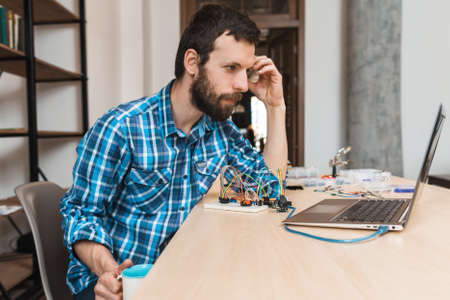 Bearded engineer waiting for program download, free space. Programmer sitting at workplace with cup of coffee and looking at laptop screen, testing new computer program Stock Photo