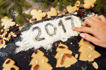 Hand writing 2017 on flour with gingerbread sweet. New year symbol on kitchen tray with traditional Christmas treat. Cooking art, design