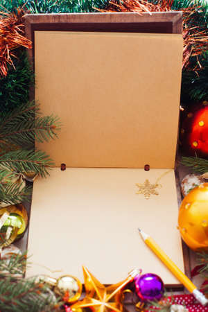Empty sketchbook with golden snowflake, xmas frame. Brown paper notebook with pencil and Christmas tree branches and trumpery, free space for text or greeting Stock Photo