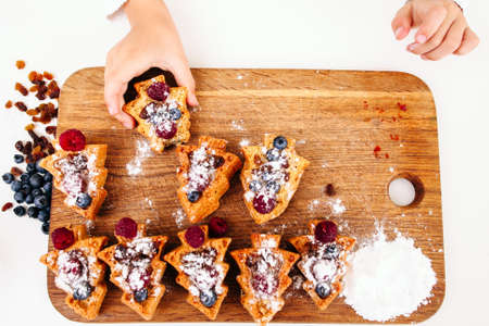 sweettooth: Child take berry cake from board, flat lay. Top view on platter with set of sweet cookies and kid hand treating on. Sweet-tooth, little monkey, pastry eating concept Stock Photo