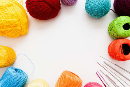 text free space: Colorful threads and knitting accessories frame, free space. Bright balls of yarn with needles and crochets on white background, copy space for text. Leisure, handiwork, hobby concept