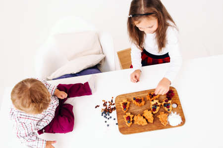 free space: Kids cooking pastry, free space. Top view on sister preparing berry cakes and her brother sitting on kitchen table. Homemade bakery, children culinary, pastry making concept Stock Photo